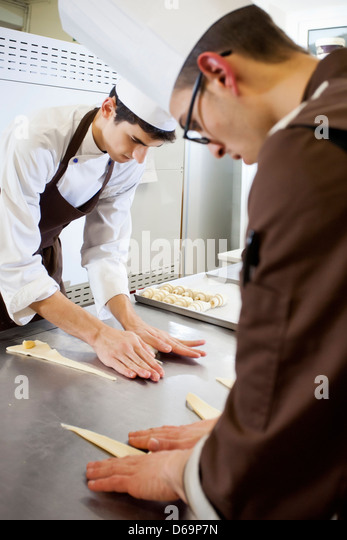 Bakers shaping dough in kitchen - Stock Image
