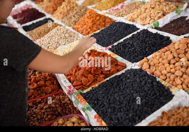 Woman selecting dried fruits and nuts on display at Shymkent Central Market Kazakhstan - Stock Image