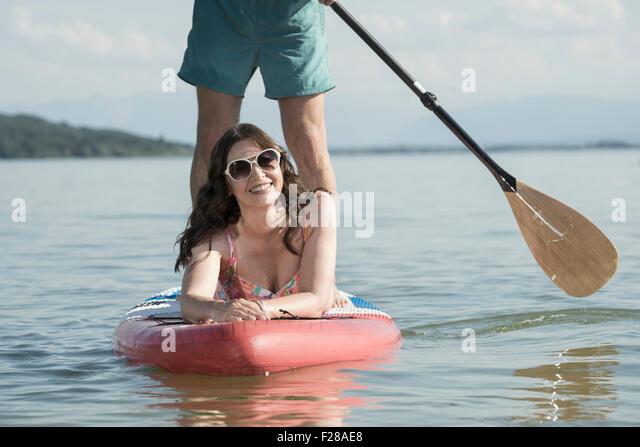 Mature couple paddleboarding in the lake, Bavaria, Germany - Stock Image