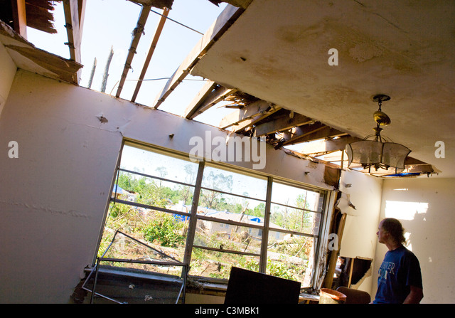 Man looks through window of his damaged home, after tornado struck his neighborhood near Tuscaloosa, Alabama, USA - Stock Image