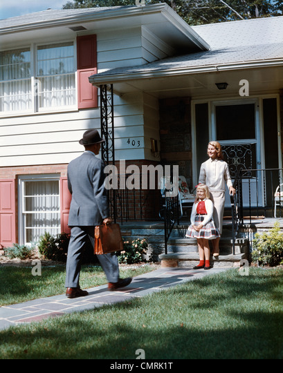 1950s MOTHER DAUGHTER WAITING STEPS HOUSE FOR FATHER BRIEFCASE COMING HOME SUBURBAN FAMILY MAN WOMAN GIRL RETRO - Stock Image