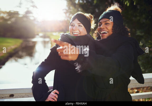 Two girlfriends laughing at something while standing in park against of river. - Stock Image