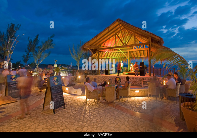 Jamaica Negril Ricks Cafe open air bar viewpoint at sunset Reggae band playing - Stock Image