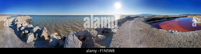 Panorama of the shoreline of the Salton Sea at Bombay Beach, California. Showing the inland sea and a pool of red - Stock Image