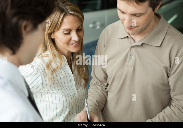 Woman watching as husband signs document - Stock Image