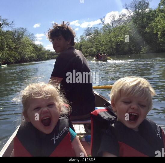 Boy girl toddler twins canoeing with uncle in Barton Creek, Austin Texas. Yelling with enthusiasm. - Stock-Bilder