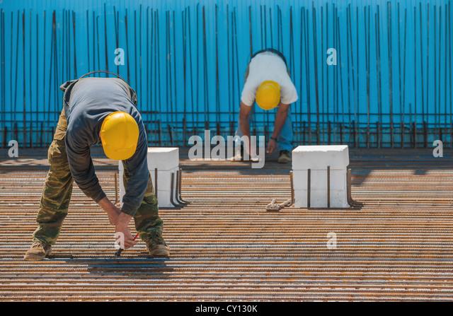 Construction workers installing binding wires to steel bars - Stock-Bilder