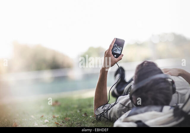 Young man lying on grass in park selecting music on smartphone - Stock Image