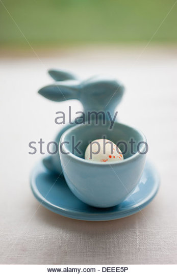 Porcelain Easter bunny and candy egg - Stock Image