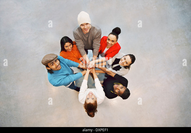Group of happy young students showing. Top view of multiethnic group of young people putting their hands together. - Stock Image
