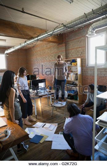 Designer standing on chair looking down at proofs and paperwork on office floor - Stock Image