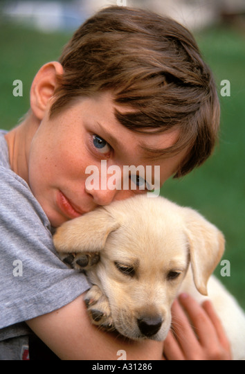young white boy holds puppy - Stock Image