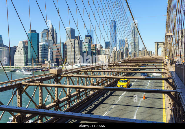 Yellow taxi cab crossing Brooklyn Bridge with the Lower Manhattan skyline behind, New York City, New York, USA - Stock Image