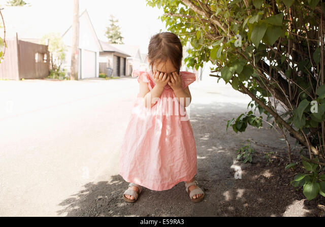 Girl covering her face outdoors - Stock Image
