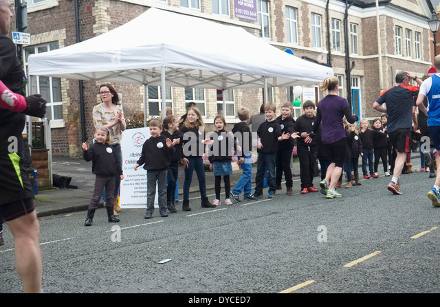 The 2014 Manchester Marathon: Runners passing members of Altrincham Childrens Choir who cheer them on - Stock Image