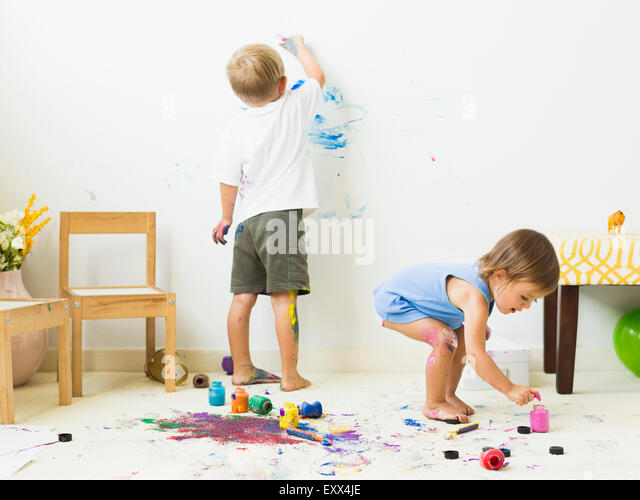 Children (2-3) painting on carpet and wall - Stock Image