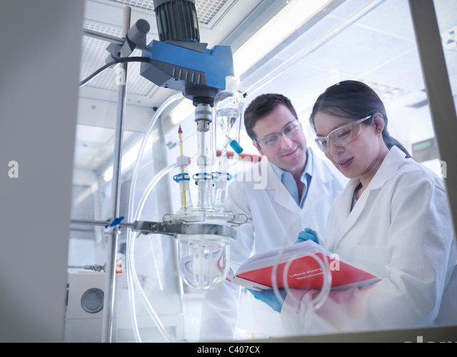 Scientists with experiment in laboratory - Stock Image