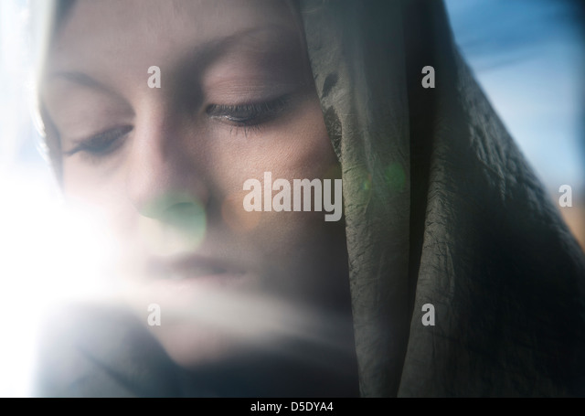 Woman wearing scarf with sun flair - Stock Image