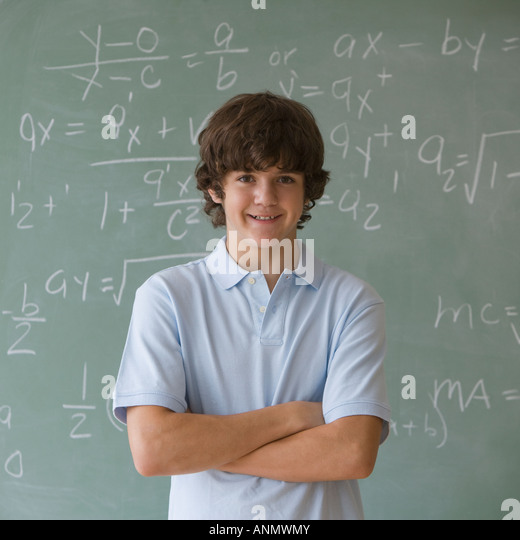 Teenaged boy in front of blackboard with math equations - Stock Image