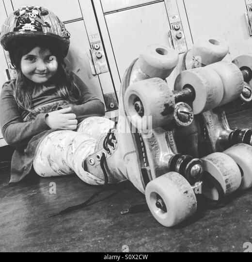 Toddler girl sitting wearing roller skates. - Stock Image