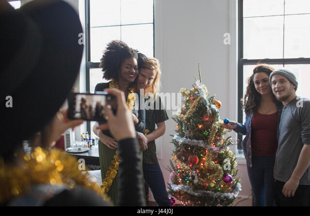 A group of people taking a photo with a Christmas tree - Stock Image