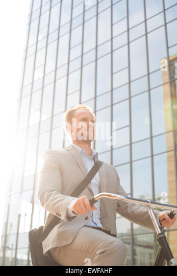 Low angle view of businessman riding bicycle outside office building on sunny day - Stock-Bilder