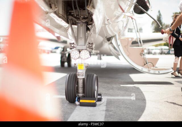 Female businesswoman leaving private jet at airport - Stock-Bilder
