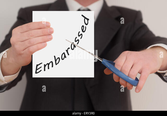 Embarassed, man in suit cutting text on paper with scissors - Stock Image