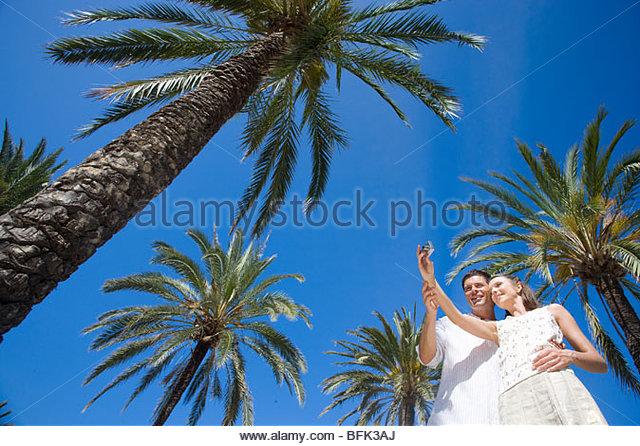 Couple taking self-portrait under palm trees - Stock Image
