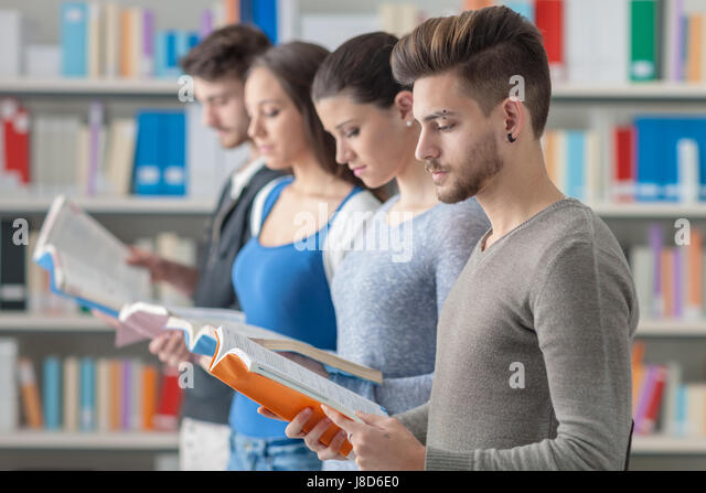 Group of college students in the library standing in line, holding books and reading, bookshelves on background - Stock Image