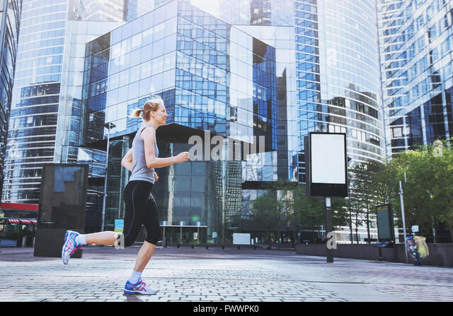 young woman running on urban background - Stock Image