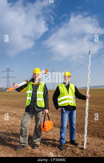 Portrait of two geodesist holding measuring equipment on construction site - Stock Image