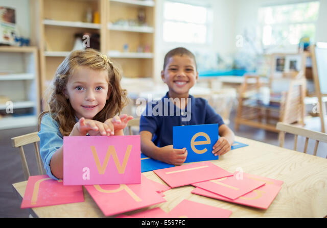 Students holding letters in classroom - Stock Image