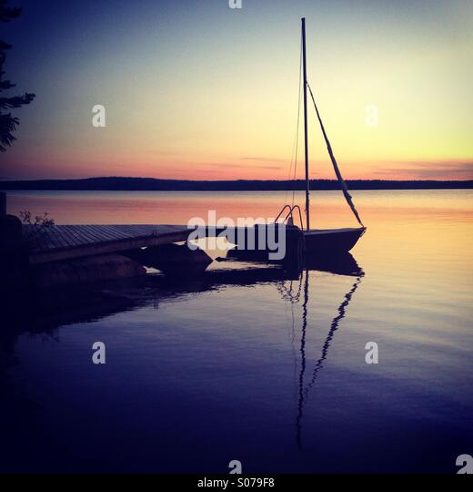 A small sailing boat moored for the night at a Finnish lake in Arctic midnight sunshine - Stock Image