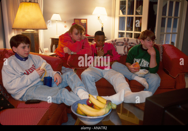 New Jersey Morris Plains teens watch television snack fruit Black male home bananas apples - Stock Image