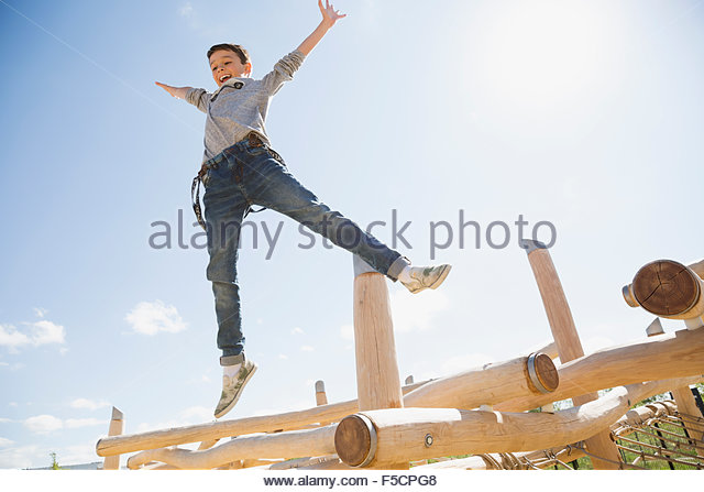 Carefree boy jumping off logs at sunny playground - Stock Image