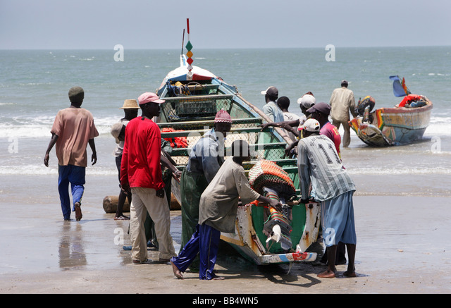 Fishermen bring a boat up onto the shore at Kap Skirring, Senegal - Stock Image