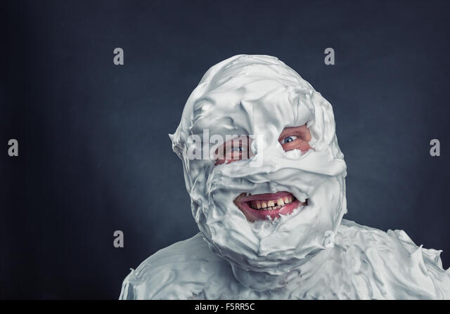 Crazy man with shaving foam on his face over grey background - Stock Image