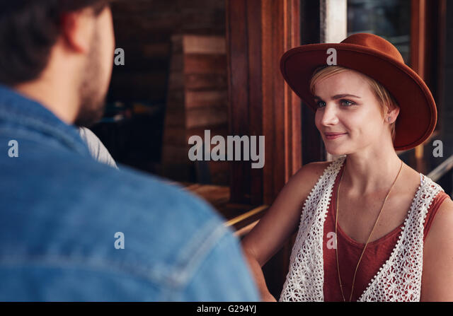 Portrait of beautiful young woman sitting at a cafe with her friend. - Stock Image