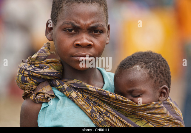 A girl carries a younger child at the Miketo IDP settlement, Katanga province, Democratic Republic of Congo - Stock-Bilder