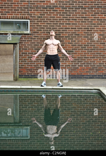 Strong professional athlete exercising by swimming pool for bodybuilding to enhance health concept, confidence, - Stock Image