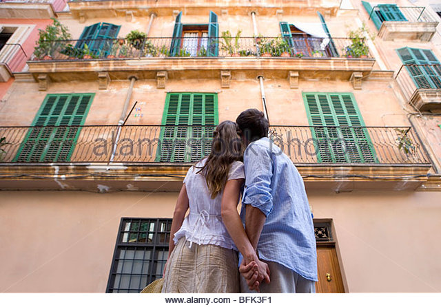 Couple holding hands and looking up at building - Stock-Bilder