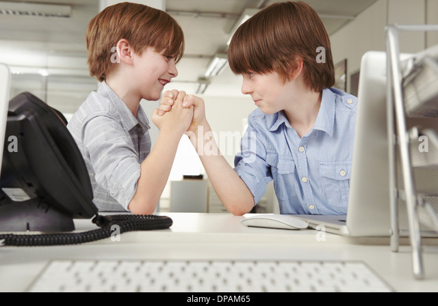 Two boys arm wrestling in office - Stock Image