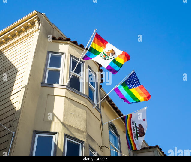A rainbow Mexican flag, rainbow American flag, and rainbow California flag hanging from a window of a building in - Stock Image
