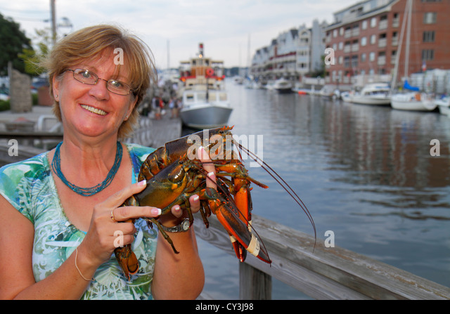 Portland Maine Historic Old Port District Long Wharf Lucky Catch Cruises lobstering excursion woman holding lobster - Stock Image
