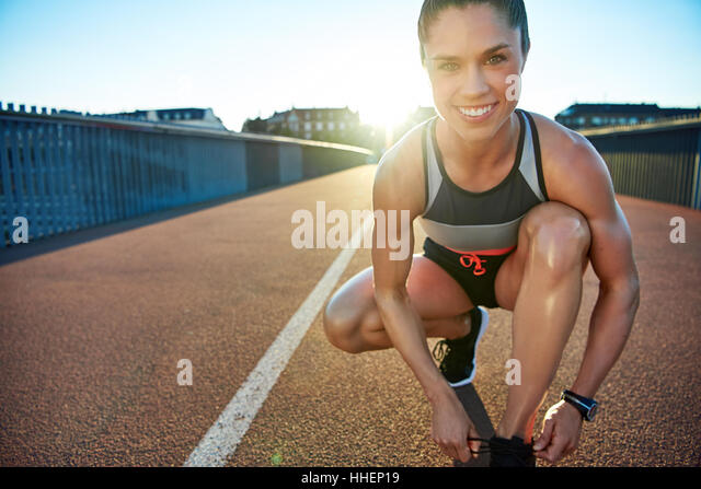 Muscular woman smiles at camera as she kneels on bridge to tie her shoes - Stock Image