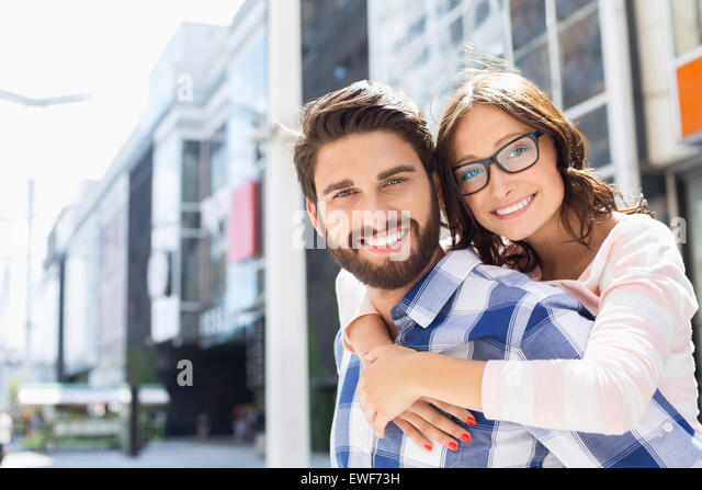 Portrait of happy man giving piggyback ride to woman in city - Stock Image