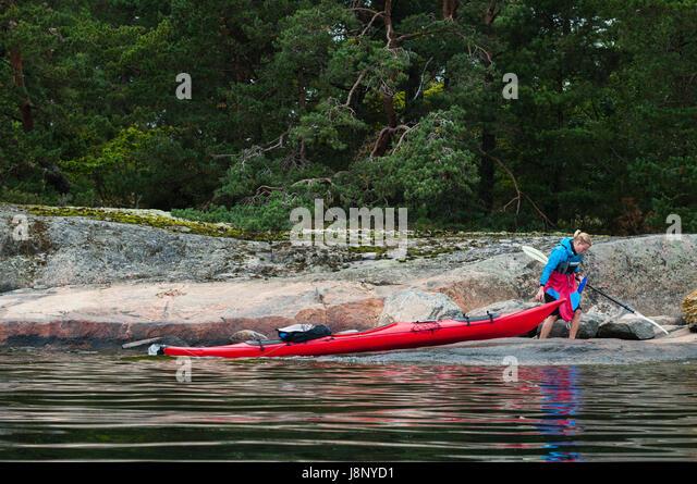 Woman pulling kayak on lakeshore - Stock-Bilder