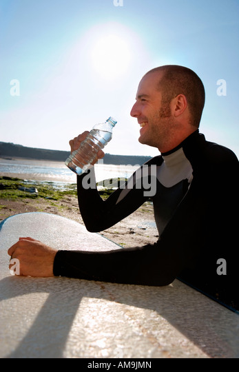 Man sitting with surfboard drinking water smiling. - Stock Image