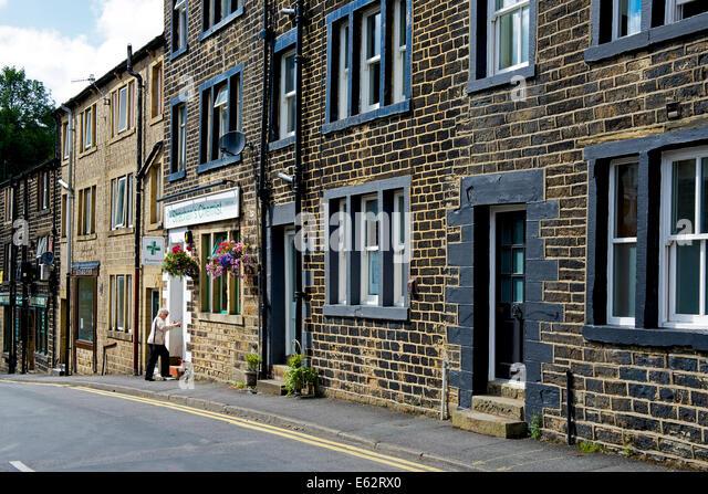 Woman walking into chemist, Uppermill, Saddleworth, West Yorkshire, England UK - Stock Image